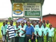 Adrian Ghele of KIBCA hands a scholarship cheque to the principal of Ringgi High School with some of the 31 recipients from the school
