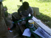 KIBCA Ranger Laeneck Vavsegaiva painting a directional sign for the Kolombangara Protected Area